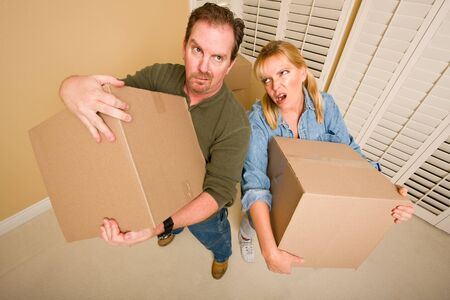 Obviously Exhausted Couple Holding Moving Boxes in Empty Room. photo