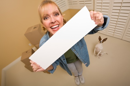 Excited Woman and Doggy with Blank Sign Near Moving Boxes in Empty Room Taken with Extreme Wide Angle Lens.  photo