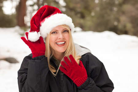 Attractive Santa Hat Wearing Blond Woman Having Fun in The Snow on a Winter Day. Stock Photo - 8688942