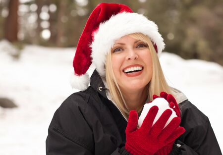 Attractive Santa Hat Wearing Blond Woman Having Fun in The Snow on a Winter Day. Stock Photo - 8688941