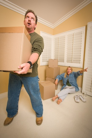 Stressed Man Moving Boxes for Demanding Wife Surrounded by Other Boxes. photo