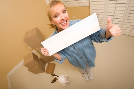 Excited Woman with Thumbs Up and Doggy Holding Blank Sign Near Moving Boxes in Empty Room Taken with Extreme Wide Angle Lens.  photo