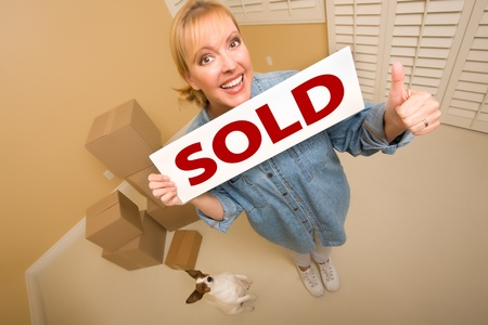 Excited Woman with Thumbs Up and Doggy Holding Sold Real Estate Sign Near Moving Boxes in Empty Room Taken with Extreme Wide Angle Lens.  photo