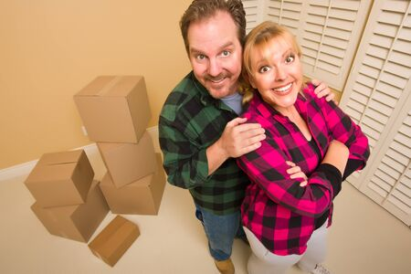 Proud Smiling Goofy Couple and Moving Boxes in Empty Room. photo
