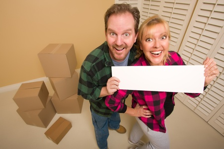 Happy Goofy Couple Holding Blank Sign in Room with Packed Boxes. Stock Photo - 8688976