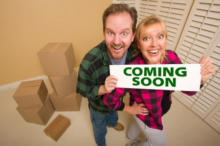 Goofy Couple Holding Coming Soon Sign in Room with Packed Cardboard Boxes. photo