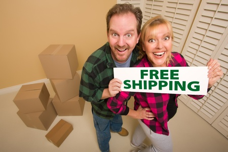 Goofy Couple Holding Free Shipping Sign in Room with Packed Cardboard Boxes. photo