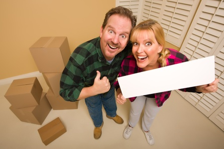 Goofy Thumbs Up Couple Holding Blank Sign in Room with Packed Cardboard Boxes. photo