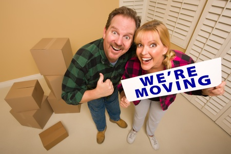 Goofy Thumbs Up Couple Holding Were Moving Sign in Room with Packed Cardboard Boxes. photo