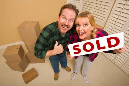 Goofy Thumbs Up Couple Holding Sold Sign in Room with Packed Cardboard Boxes. photo