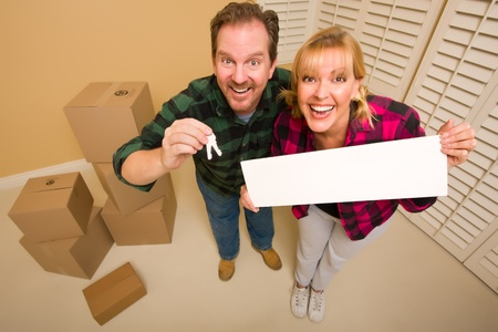 Goofy Couple Holding Keys and Blank Sign in Room with Packed Cardboard Boxes. photo