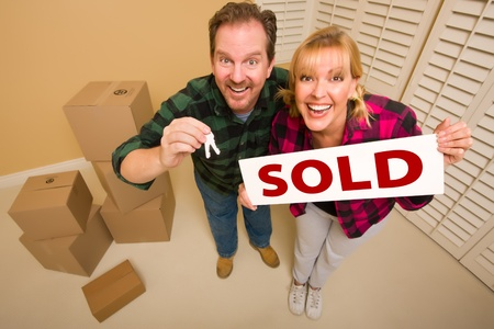 Goofy Couple Holding Key and Sold Sign in Room with Packed Cardboard Boxes. photo