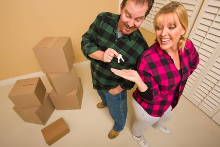 Goofy Excited Man Handing Keys to Smiling Wife in Room with Packed Boxes. photo