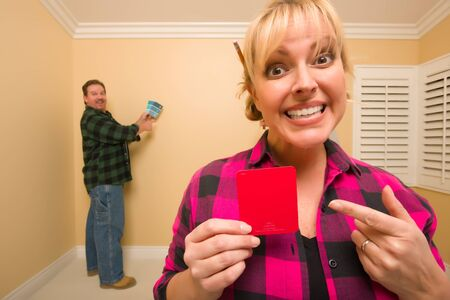 Fun Happy Couple Comparing Paint Colors in Empty Room - Woman Large, in Front, Man Smaller, Behind. photo
