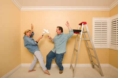 Fun Couple Playing Sword Fight with Paint Rollers in Room - Ladder and Paint Tray Near. photo