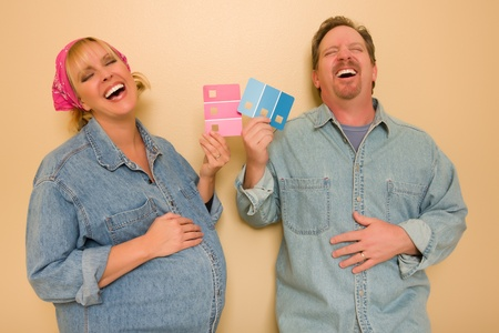 Laughing Man and Pregnant Woman Deciding on Pink or Blue Wall Paint with Swatches in Hand.  photo