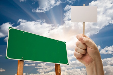 Blank Green Road Sign and Man Holding Poster on Stick Over Blue Sky and Clouds. photo