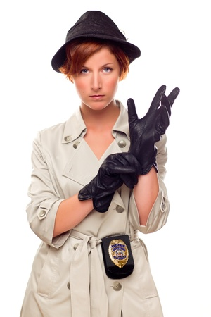 Red Haired Female Detective Putting on Gloves Wearing a Badge, Trenchcoat and Hat Isolated on a White Background. photo