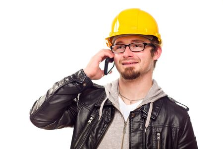 Handsome Young Man in Hard Hat Talking on Cell Phone Isolated on a White Background. photo