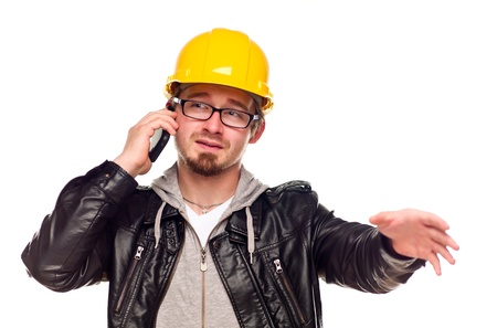 Handsome Young Man in Hard Hat Talking on Cell Phone Isolated on a White Background. Stock Photo - 8923978