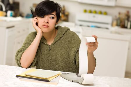 Multi-ethnic Young Woman Agonizing Over Financial Calculations in Her Kitchen. photo