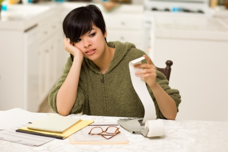 debt: Multi-ethnic Young Woman Agonizing Over Financial Calculations in Her Kitchen.