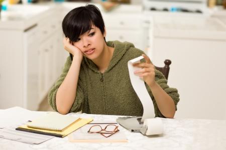 schuld: Multi-etnische jonge vrouw kwellende Over financiële berekeningen in haar keuken.