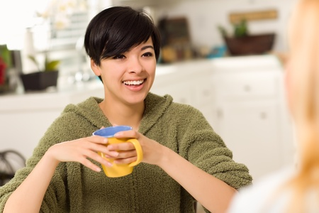 Multi-ethnic Young Attractive Woman Socializing with Friend in Her Kitchen. photo