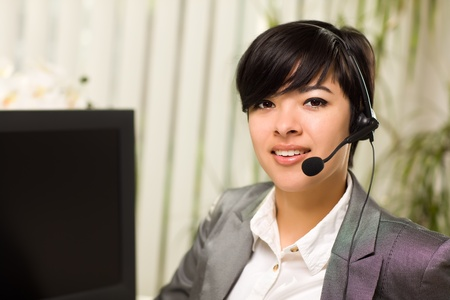 Attractive Young Woman Smiles Wearing Headset Near Her Computer Monitor. photo
