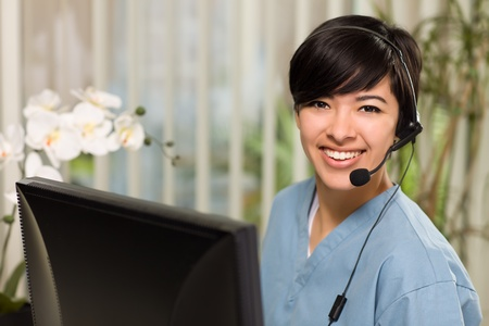 headset help: Smiling Attractive Multi-ethnic Young Woman Wearing Headset and Scrubs Near Her Computer Monitor. Stock Photo