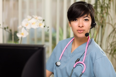 Smiling Attractive Multi-ethnic Young Woman Wearing Headset, Scrubs and Stethoscope Near Her Computer Monitor. photo