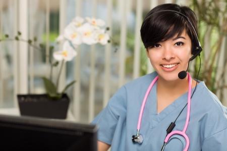 telephone headsets: Sonriendo atractiva joven multi�tnica usando auriculares, matorrales y estetoscopio cerca de su ordenador. Foto de archivo