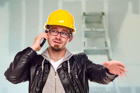 tablaroca: Contratista de j�venes con sombrero duro en celular en casa inconclusa con yeso y escalera en segundo plano.