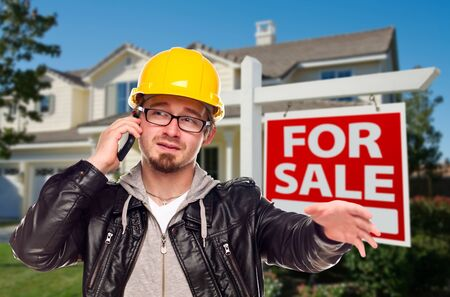 Contractor in Hard Hat in Front of House and For Sale Real Estate Sign. photo