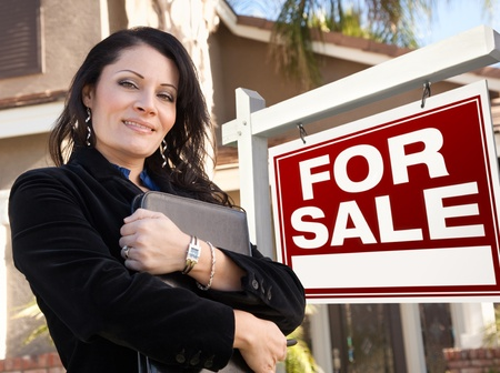 sell: Proud, Attractive Hispanic Female Agent In Front of For Sale Real Estate Sign and House. Stock Photo