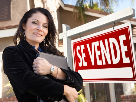 Proud, Attractive Hispanic Female Agent In Front of Spanish Se Vende Real Estate Sign and House. photo