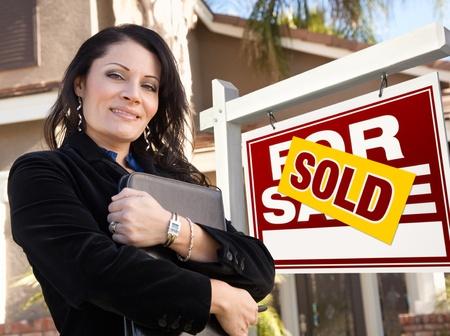 real estate sold: Orgulloso, atractivo hispanos agente femenina de vendido para venta inmobiliaria signo y casa. Foto de archivo