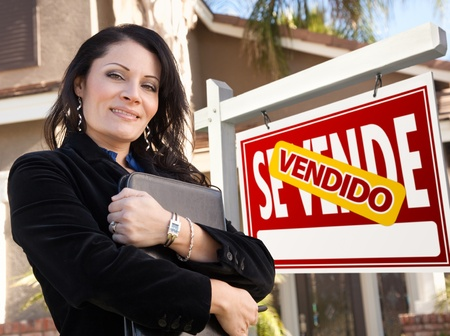 se: Proud, Attractive Hispanic Female Agent In Front of Spanish Vendido Se Vende Real Estate Sign and House.