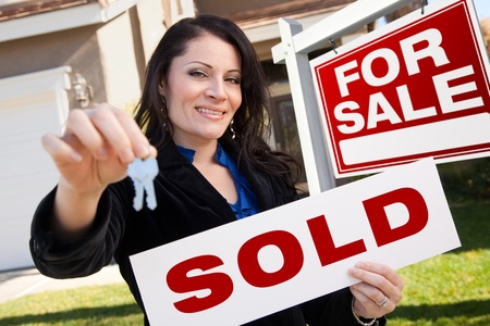 Happy Attractive Hispanic Woman Holding Sold Real Estate Sign and Keys in Front For Sale Real Estate Sign and House.