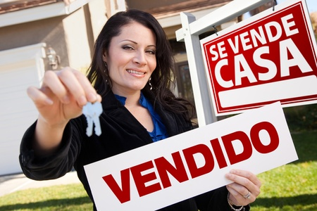 Happy Attractive Hispanic Woman Holding Vendido Real Estate Sign and Keys in Front Se Vende Casa Real Estate Sign and House. Фото со стока