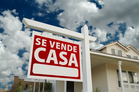 Se Vende Casa Spanish Real Estate Sign and House and Blue Sky with Clouds. photo