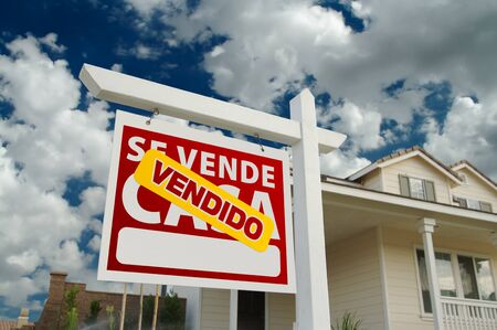 Vendido Se Vende Casa Spanish Real Estate Sign and House and Blue Sky with Clouds. photo