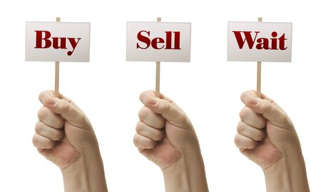 Three Signs In Male Fists Saying Buy, Sell and Wait Isolated on a White Background. photo