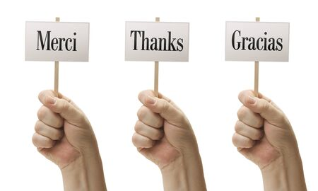 Three Signs In Male Fists Saying Merci, Thanks and Gracias Isolated on a White Background. photo