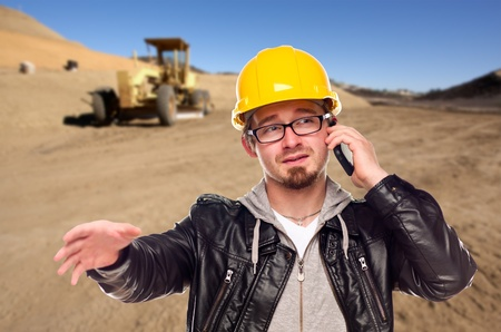 Young Cunstruction Worker on Cell Phone in Dirt Field with Tractor in the Background.