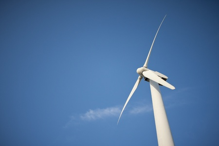 Single Wind Turbine Over Dramatic Blue Sky and Clouds. photo