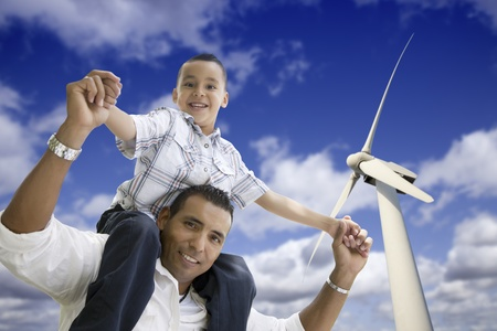 Happy Hispanic Father and Son with Wind Turbine Over Blue Sky. photo