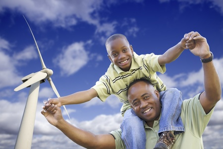 Happy African American Father and Son with Wind Turbine Over Blue Sky. photo