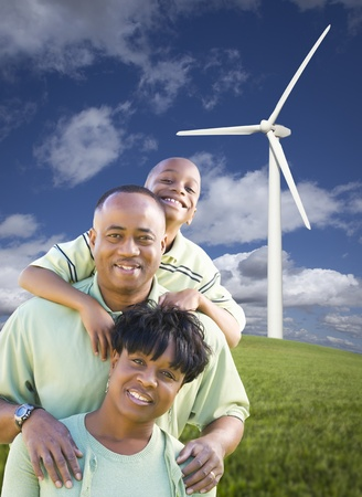 Happy African American Family and Wind Turbine with Dramatic Sky and Clouds. photo
