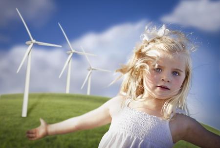 turbina: Hermosa joven jugando cerca de turbinas e�licas y campo de hierba. Foto de archivo